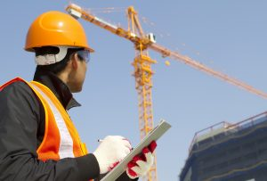 Construction worker with crane on background